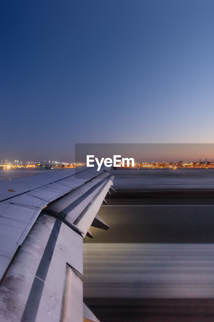sky, transportation, air vehicle, airplane, mode of transportation, nature, aircraft wing, copy space, architecture, no people, clear sky, travel, sunset, building exterior, built structure, city, blue, airport, illuminated, outdoors