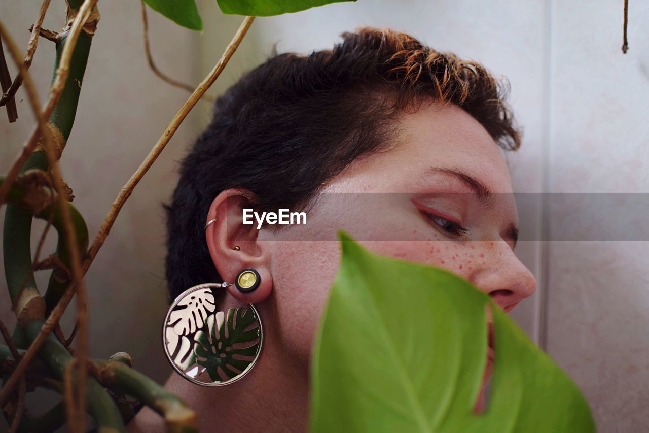 Young woman wearing earring by plants