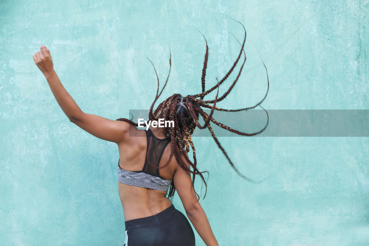 Woman with braided hair dancing against blue wall