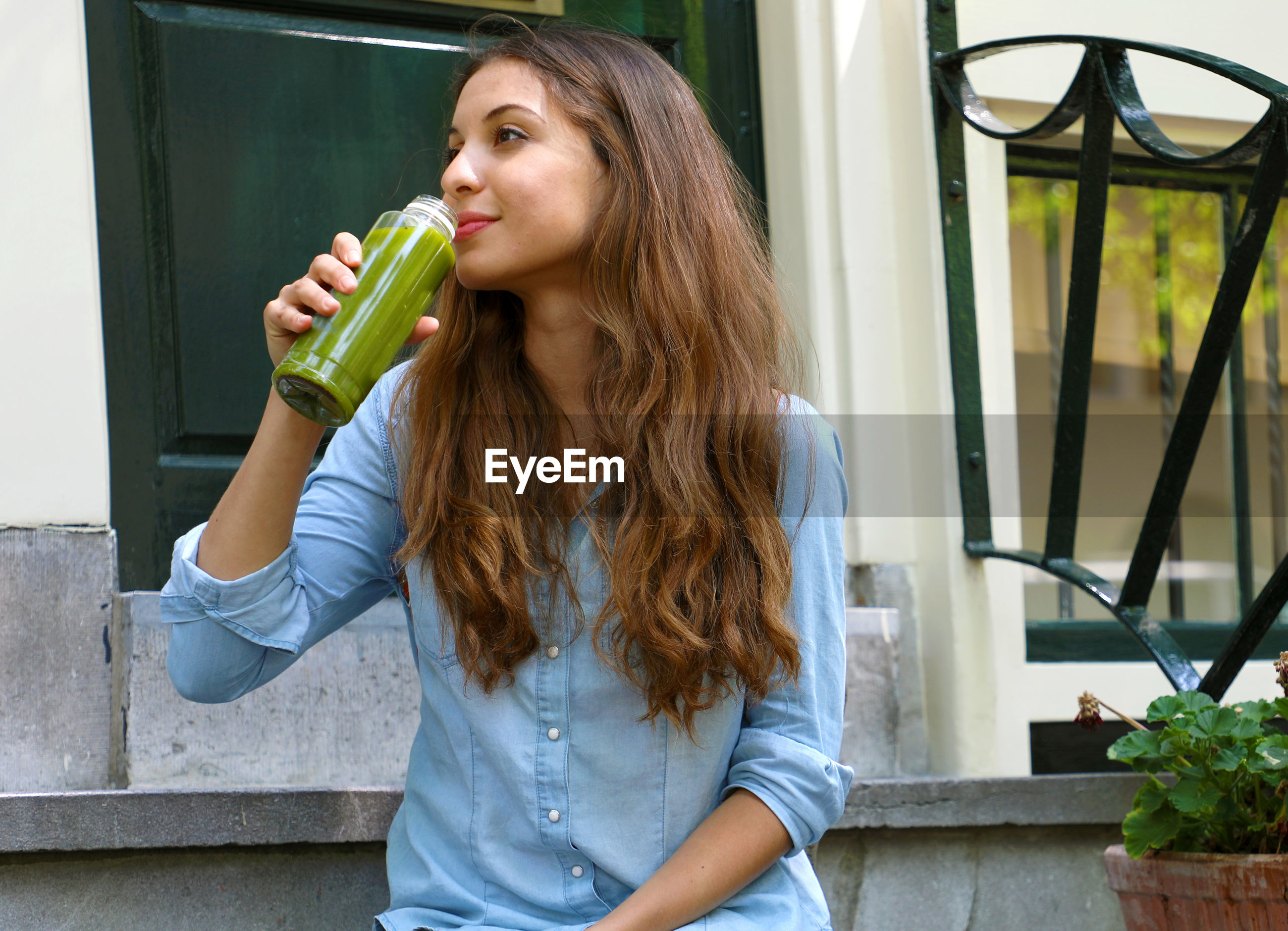 Thoughtful woman having drink while sitting outdoors