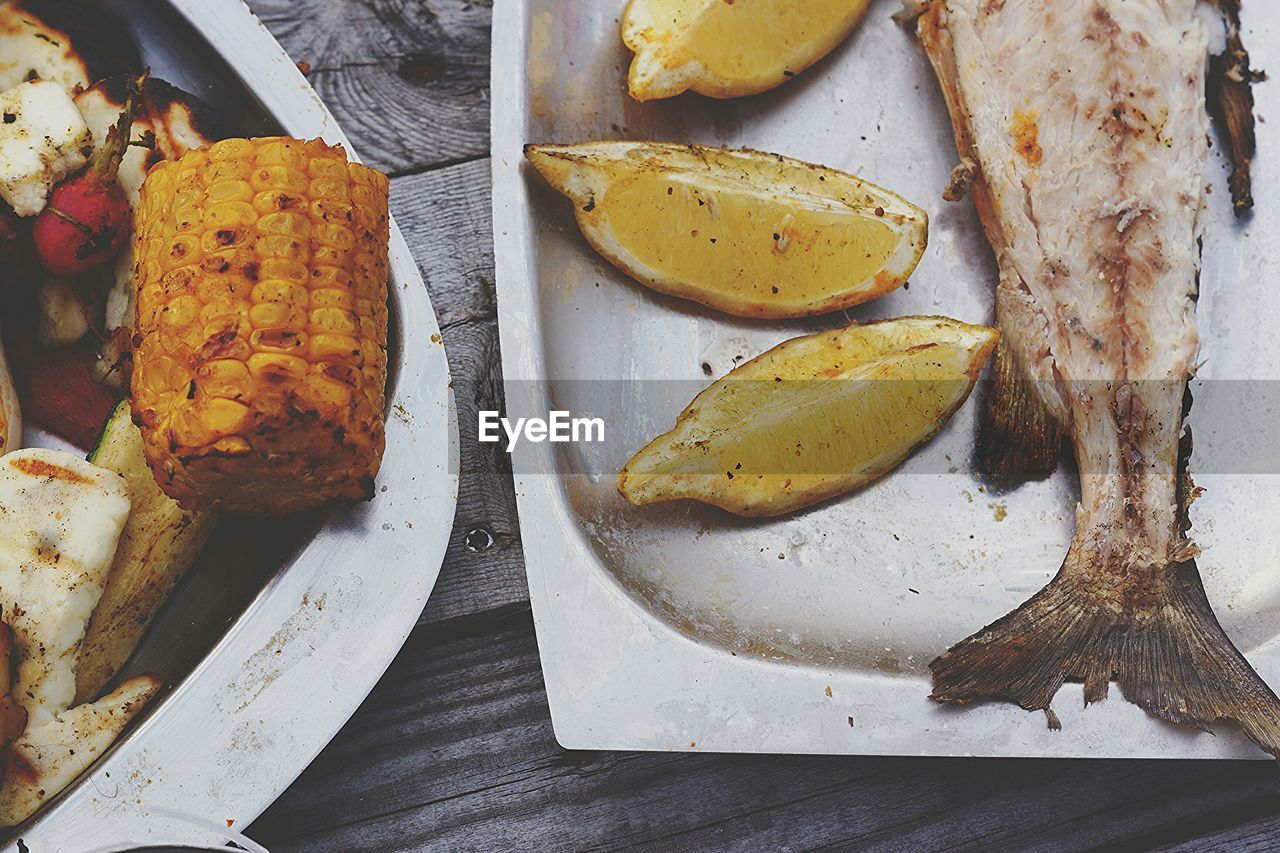 High Angle View Of Fish And Lemons In Plate On Table