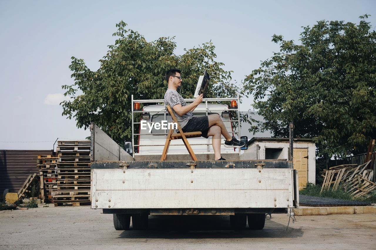 Side view of man sitting on chair in semi-truck