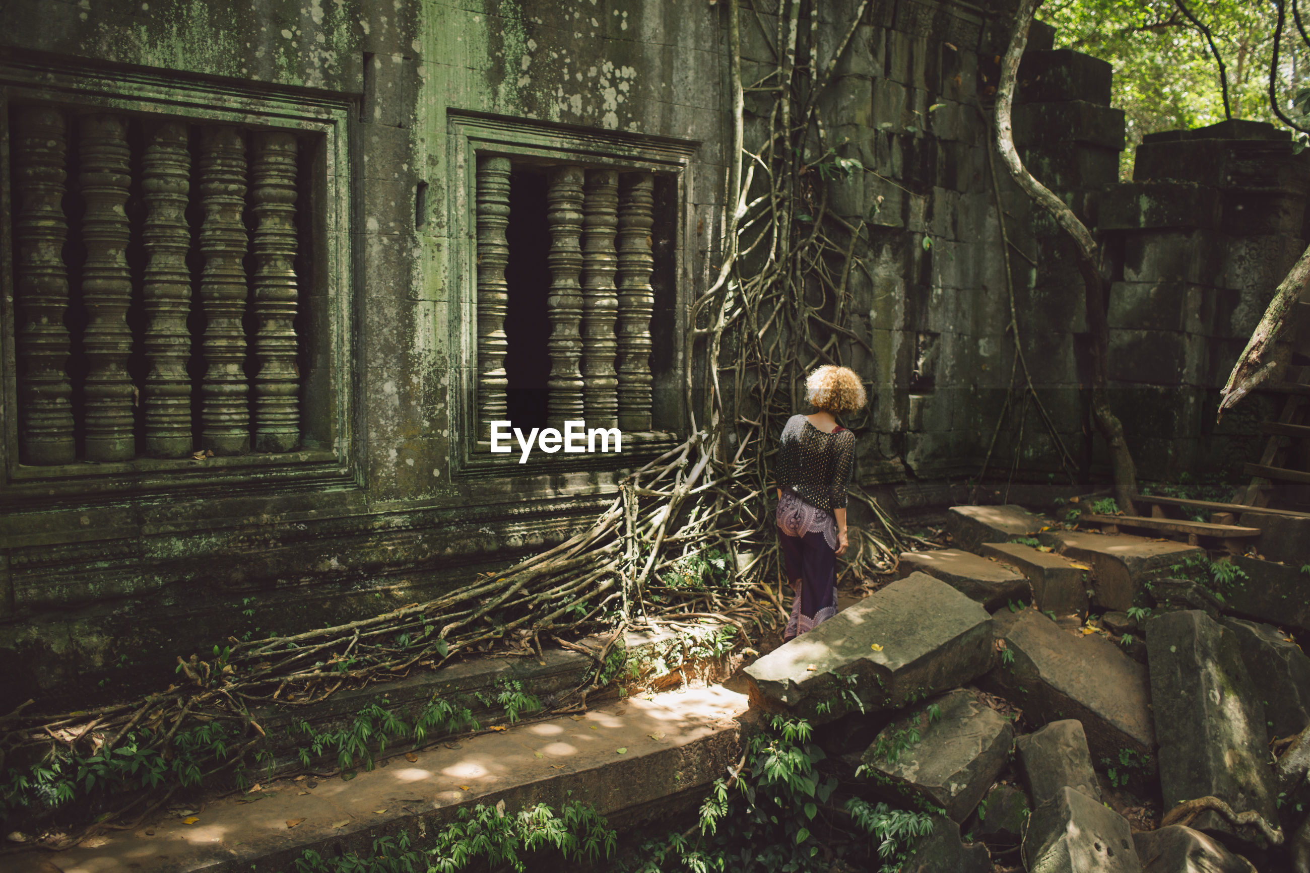 Rear view of woman at old ruins in forest