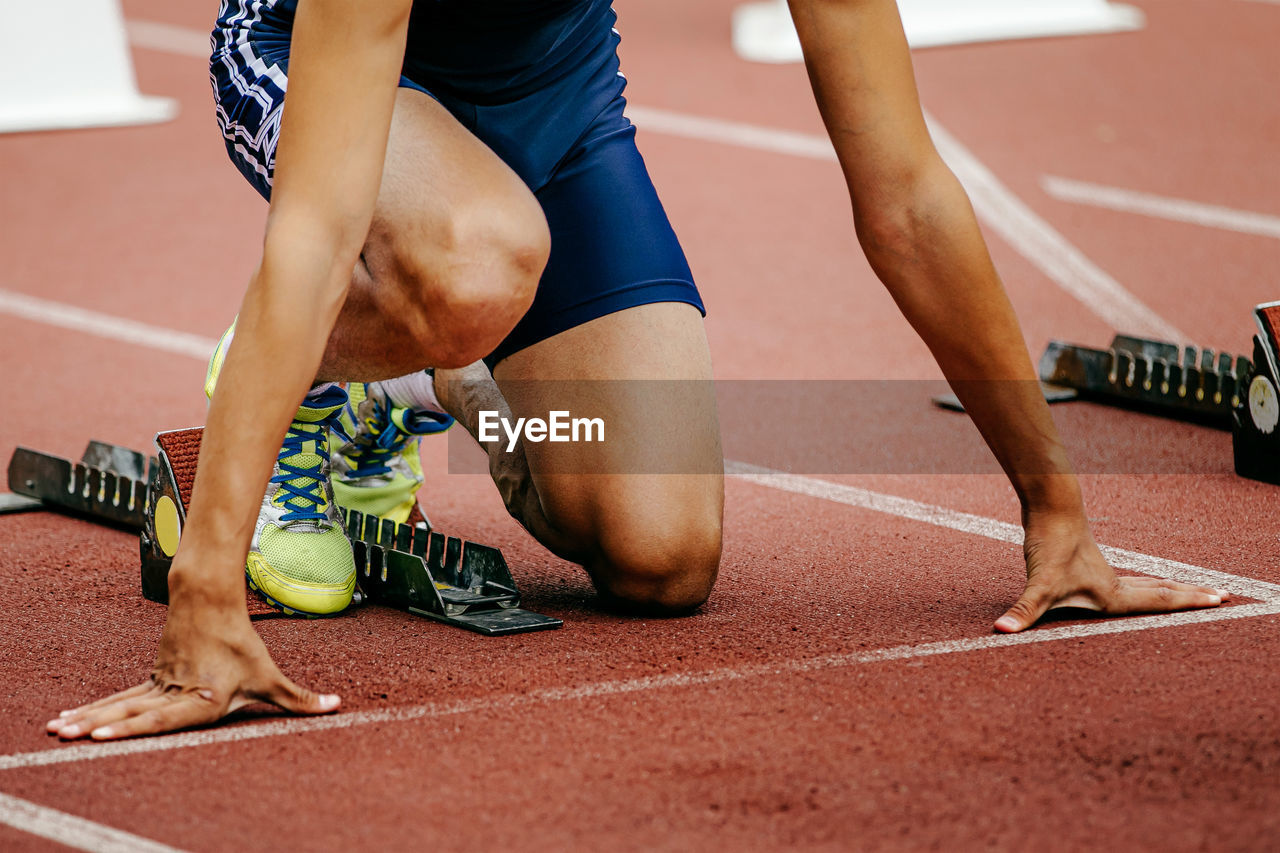 Low section of runner crouching on running track