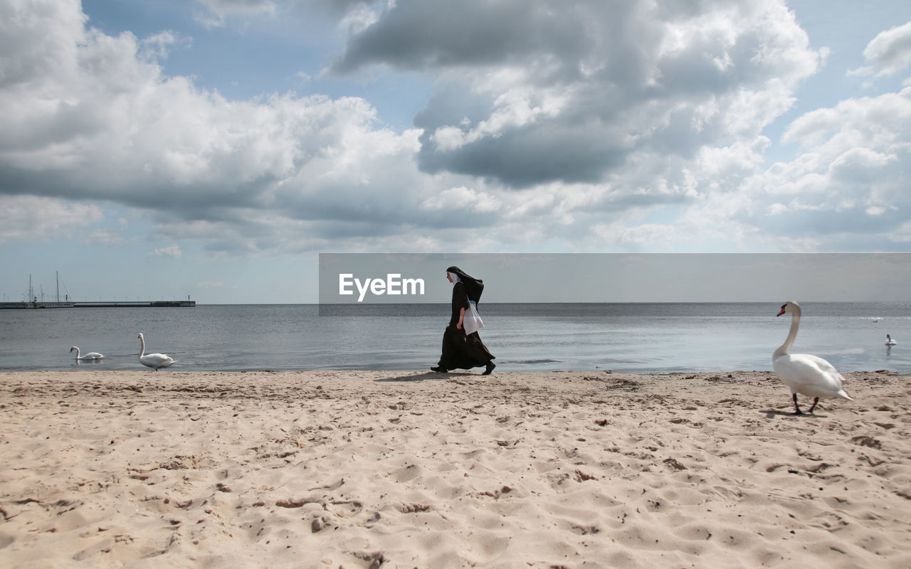 sea, beach, sky, sand, nature, horizon over water, water, cloud - sky, beauty in nature, real people, day, scenics, outdoors, full length, standing, bird, tranquility, one person, men, people