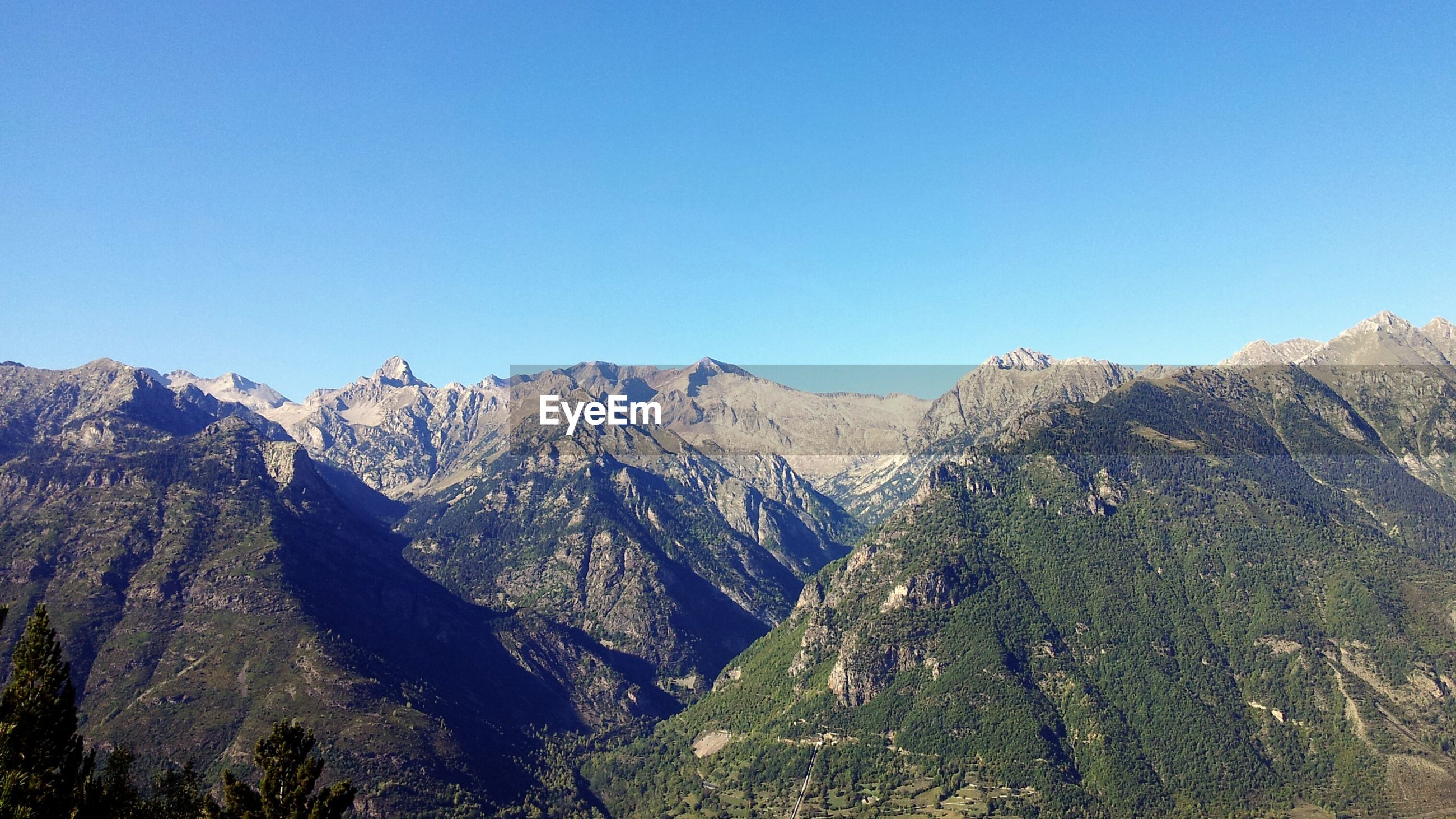 Scenic shot of rocky mountain range against clear blue sky
