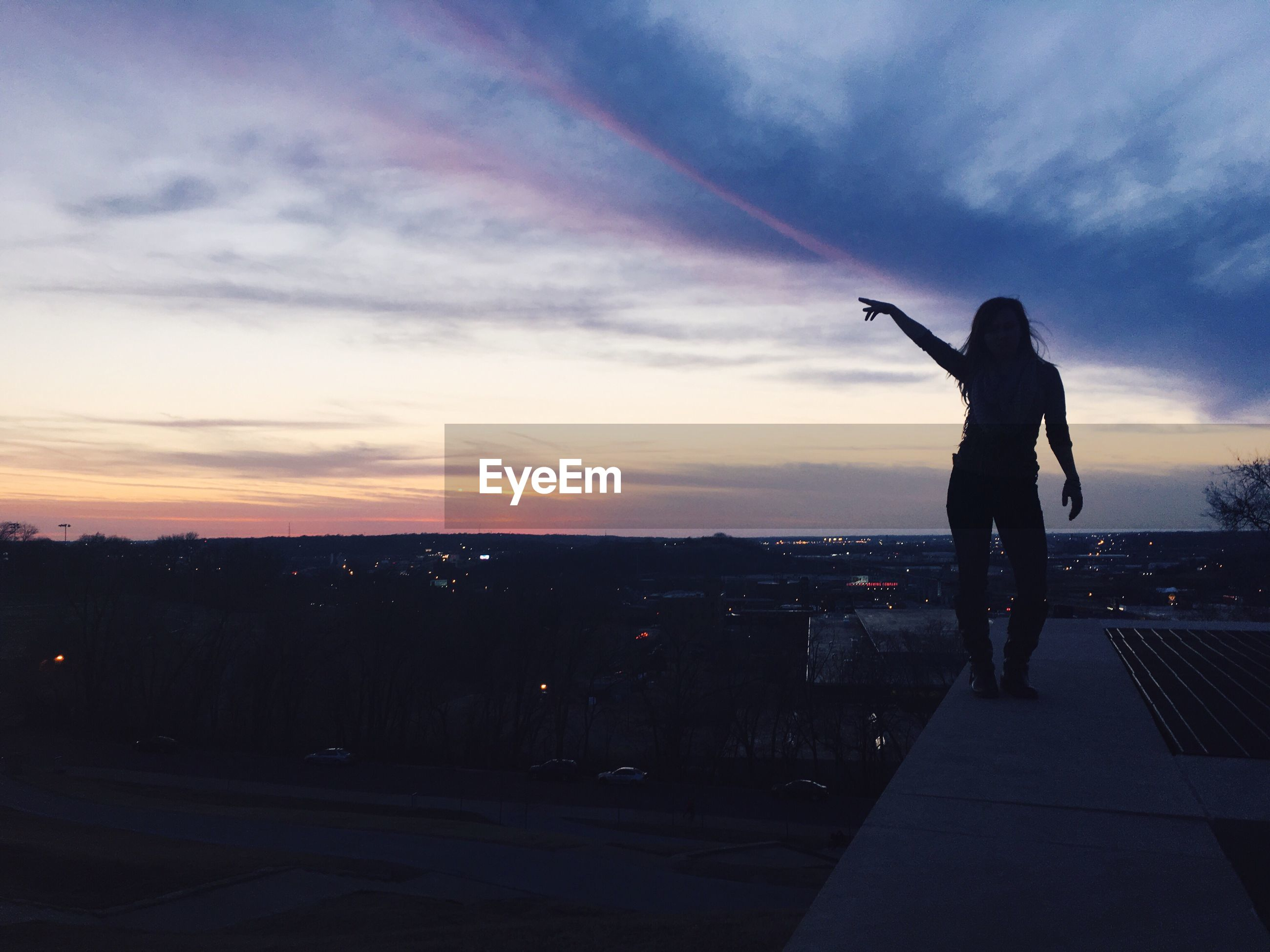 Silhouette woman pointing while standing on retaining wall against sky during sunset
