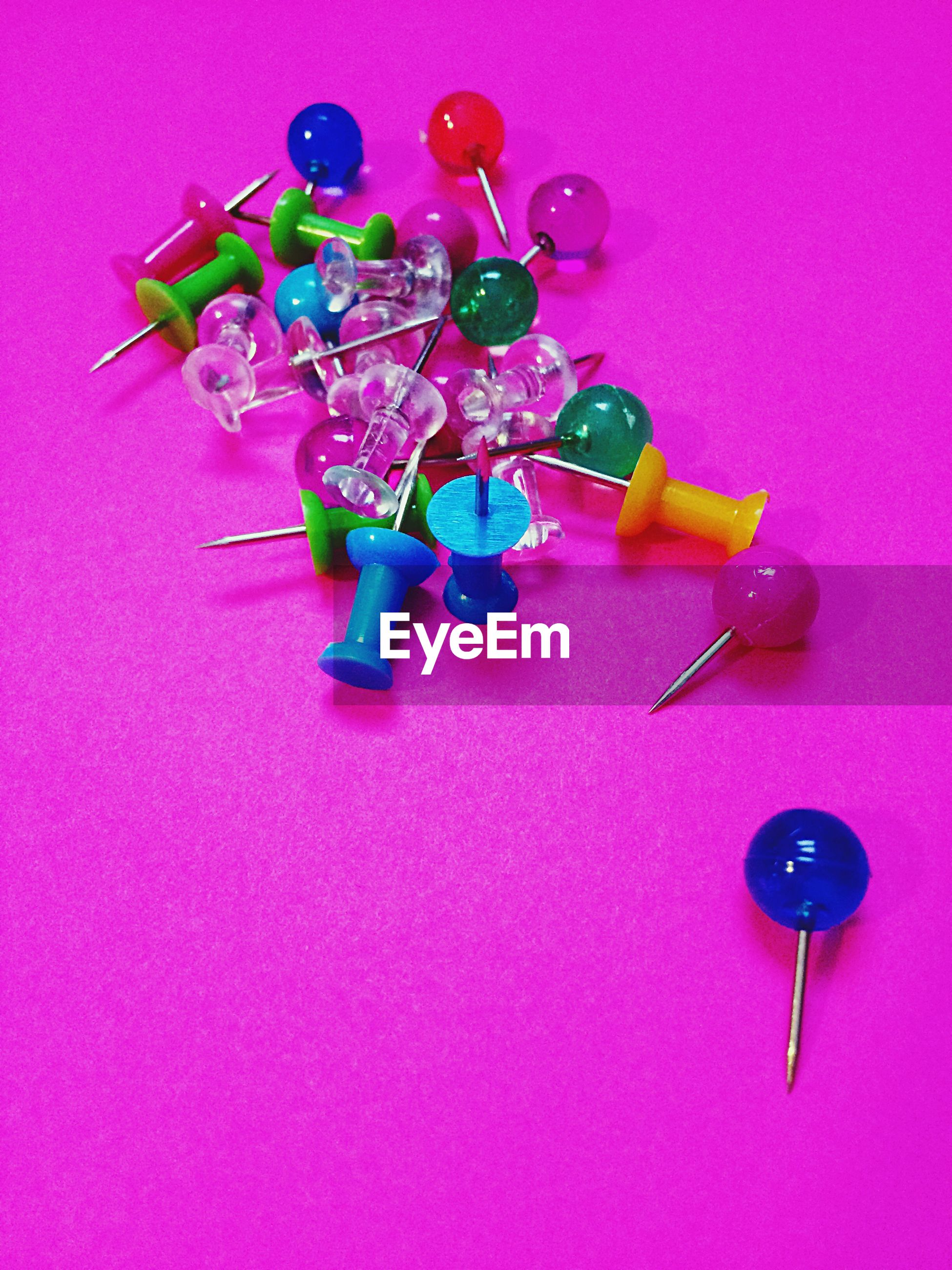 Close-up of multi colored thumbtacks on pink background