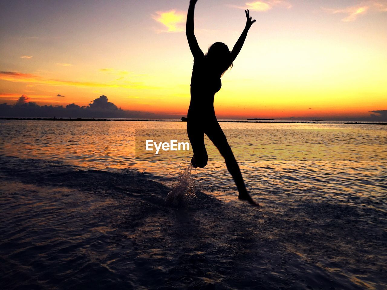 sunset, silhouette, water, sea, real people, nature, beauty in nature, full length, beach, scenics, one person, sky, leisure activity, fun, balance, horizon over water, outdoors, lifestyles, jumping, skill, motion, handstand, flexibility, people