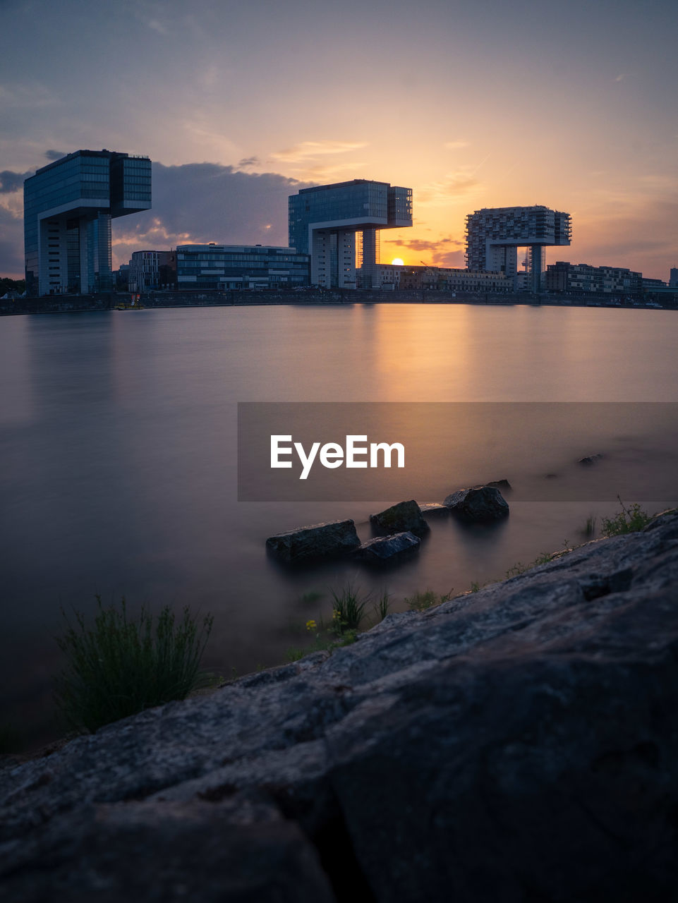 Scenic View Of River By Buildings Against Sky At Sunset