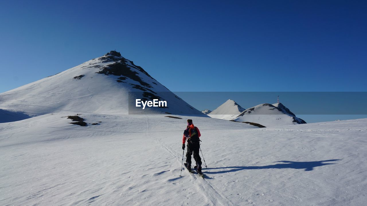 Rear View Of Person Skiing On Snowcapped Mountain Against Clear Sky