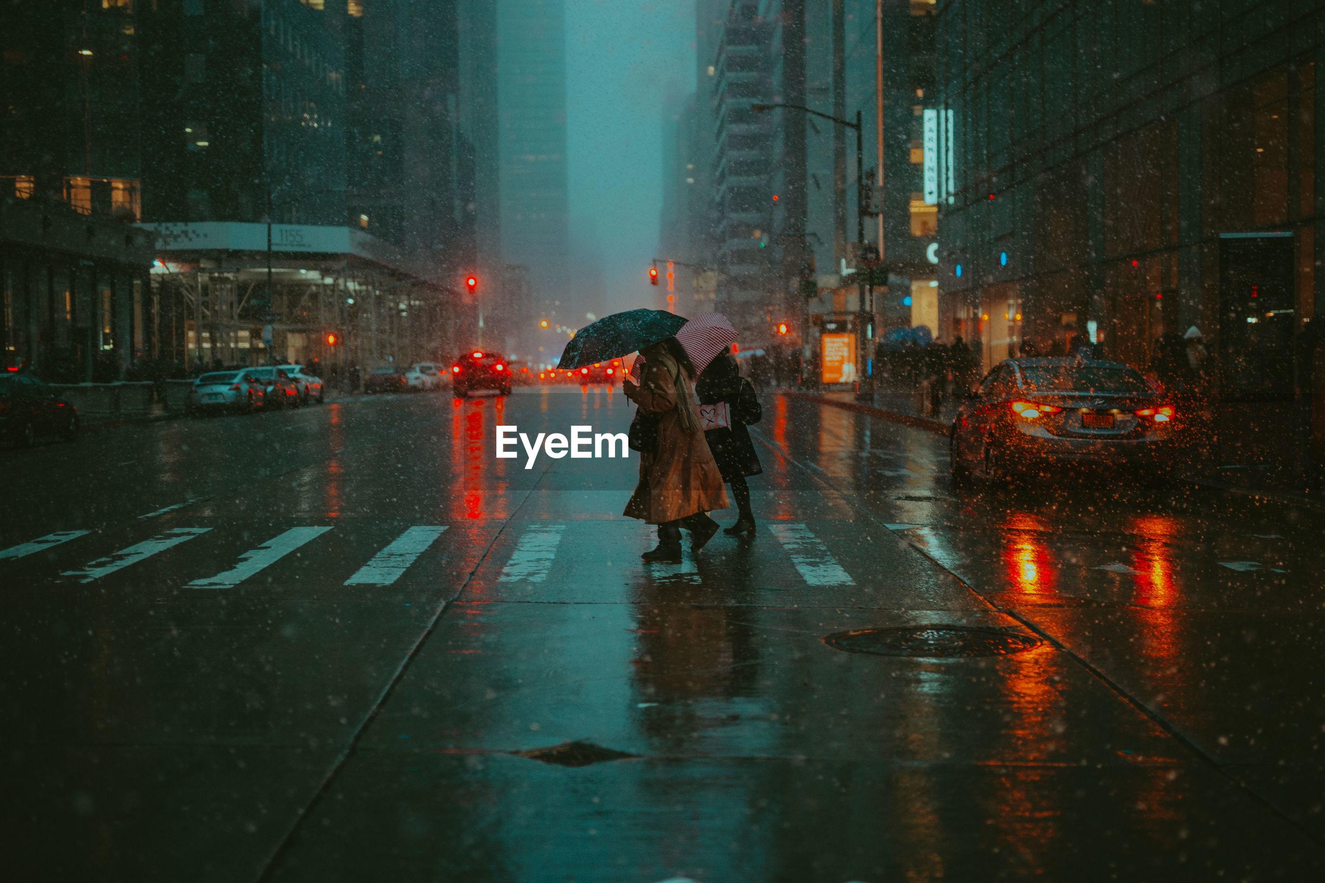 PEOPLE WALKING ON WET ROAD IN RAIN