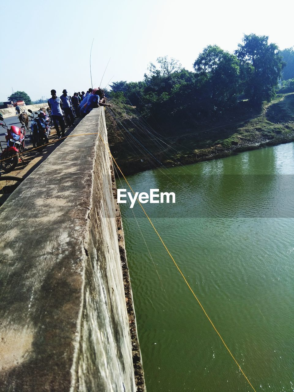 water, sky, plant, tree, nature, group of people, day, real people, river, transportation, direction, men, bridge, built structure, architecture, lifestyles, incidental people, the way forward, connection, outdoors
