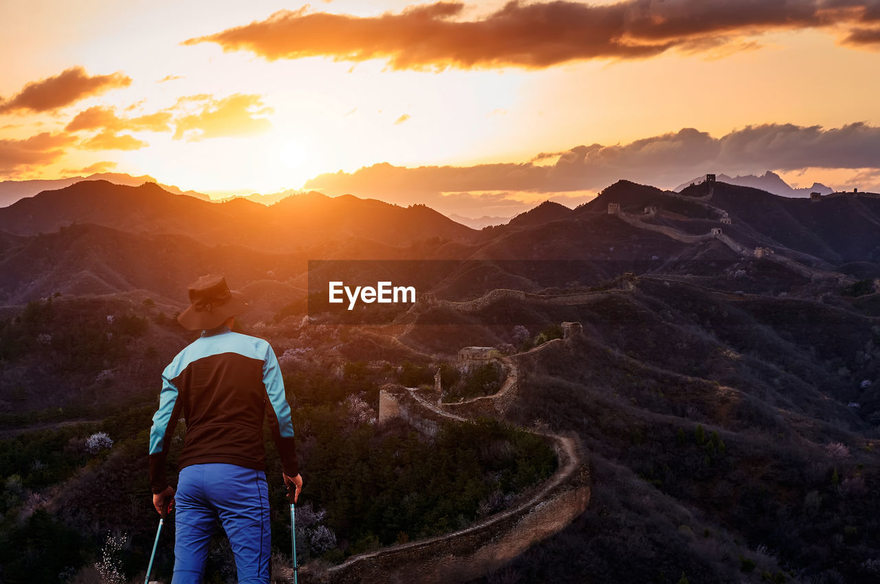 Rear View Of Man Looking At Mountains During Sunset