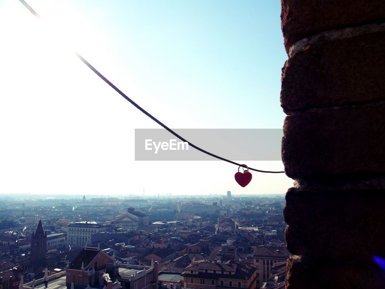 Heart shaped padlock hanging from cable over cityscape against sky