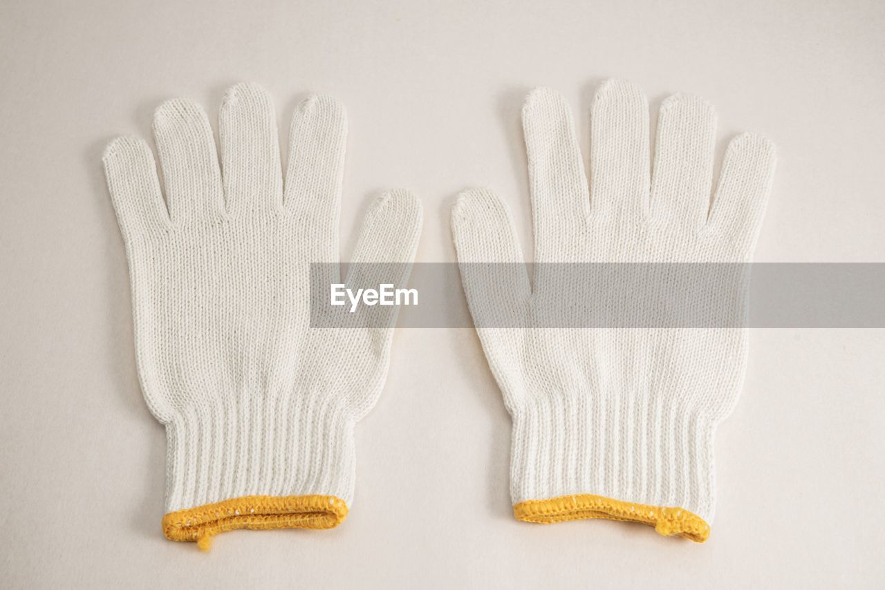 High angle view of knit gloves over white background