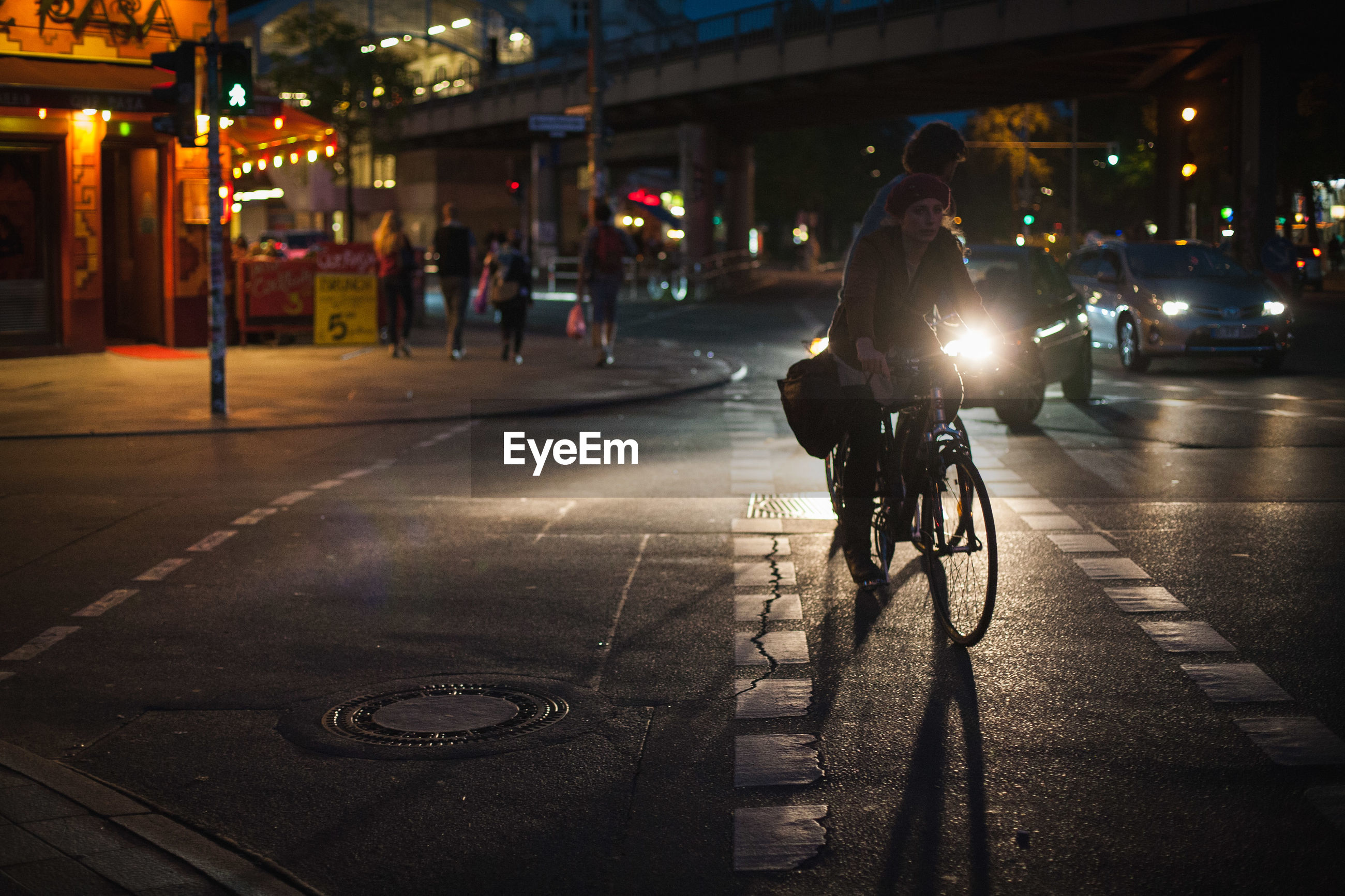 PEOPLE RIDING BICYCLES ON ROAD AT NIGHT