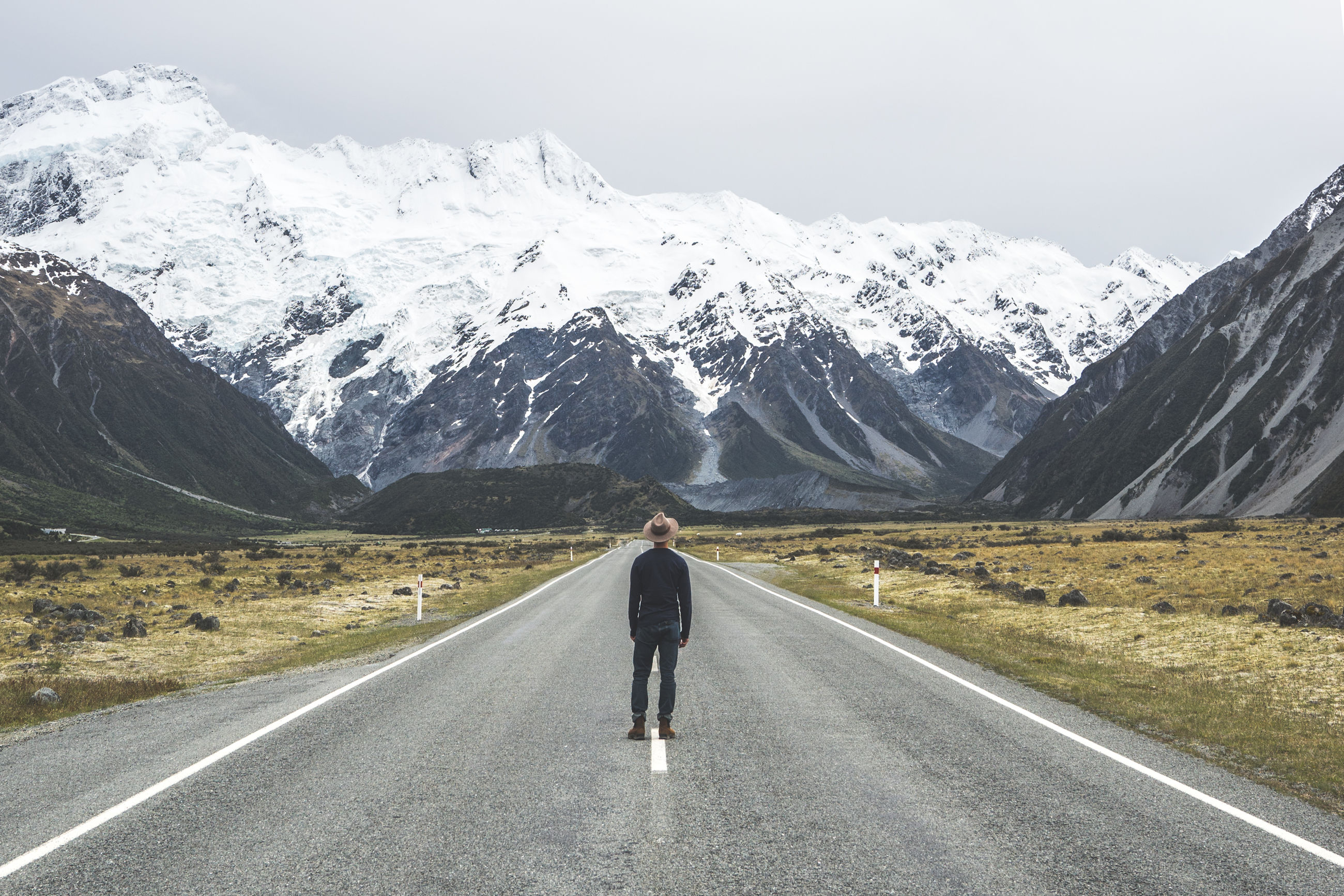 Rear view of man standing on road against snowcapped mountain