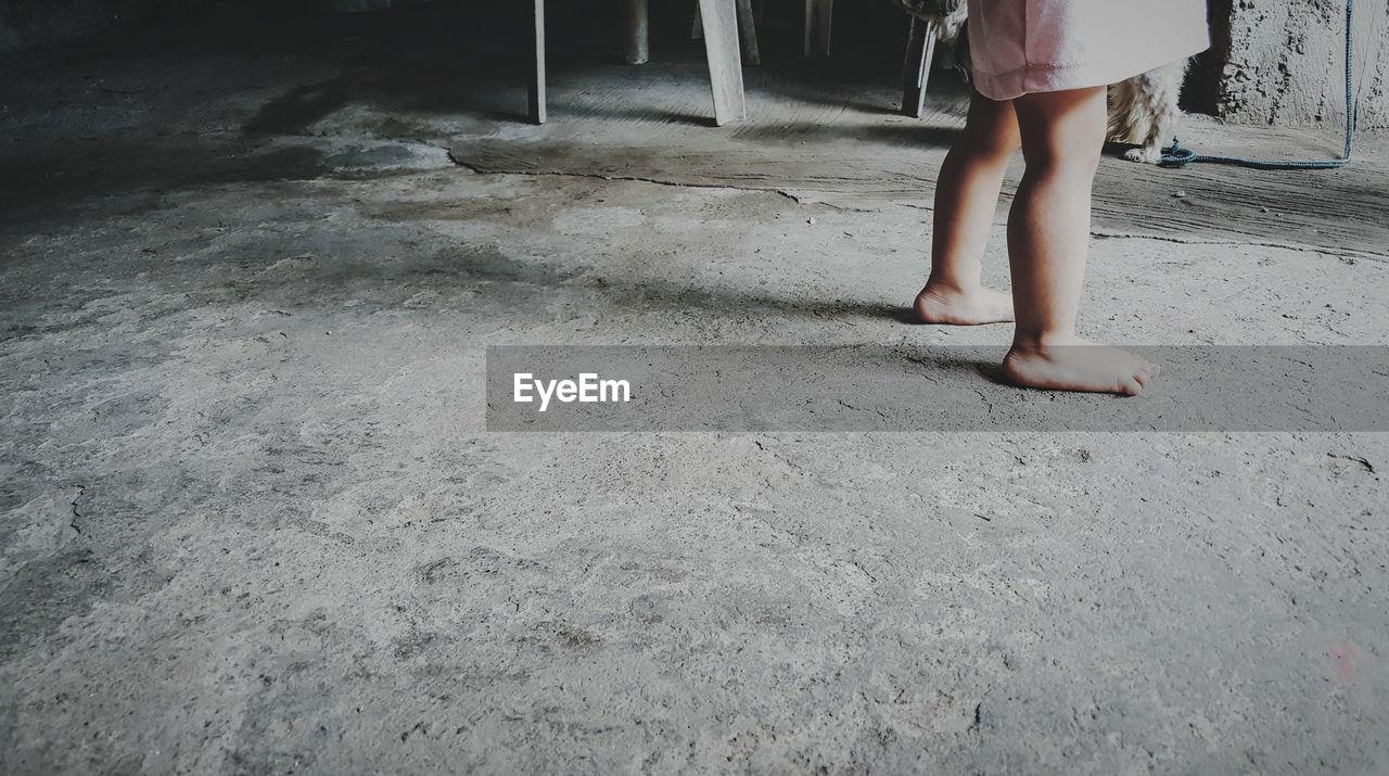 Low section of kid standing floor