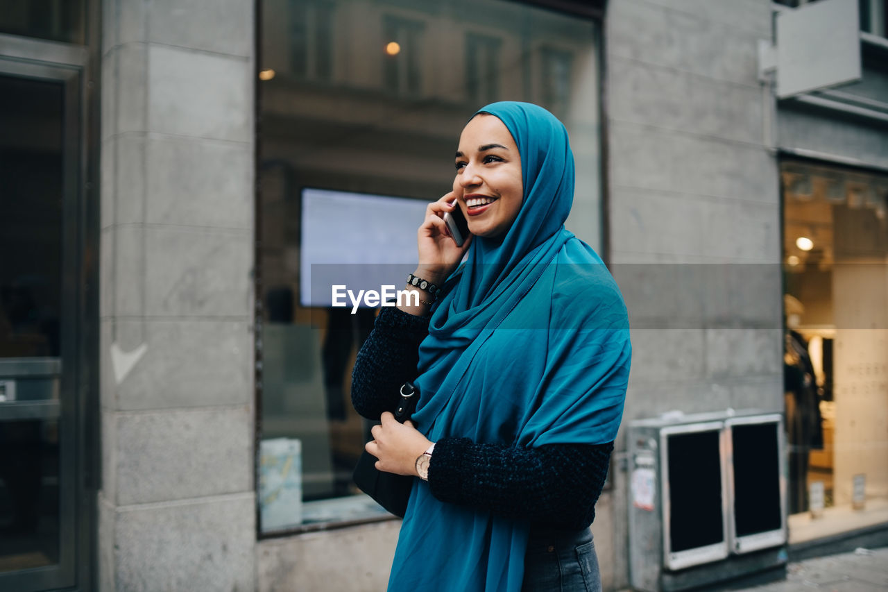 technology, one person, communication, young adult, wireless technology, standing, holding, mobile phone, real people, using phone, architecture, focus on foreground, waist up, connection, built structure, young women, building exterior, talking, women, listening, hijab, beautiful woman