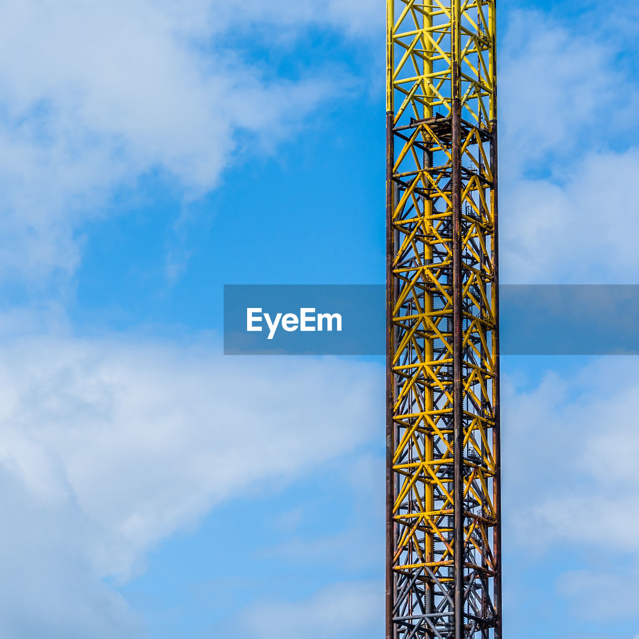 cloud - sky, sky, built structure, low angle view, architecture, day, metal, tower, no people, nature, tall - high, outdoors, industry, blue, crane - construction machinery, construction industry, yellow, construction site, focus on foreground, development, construction equipment