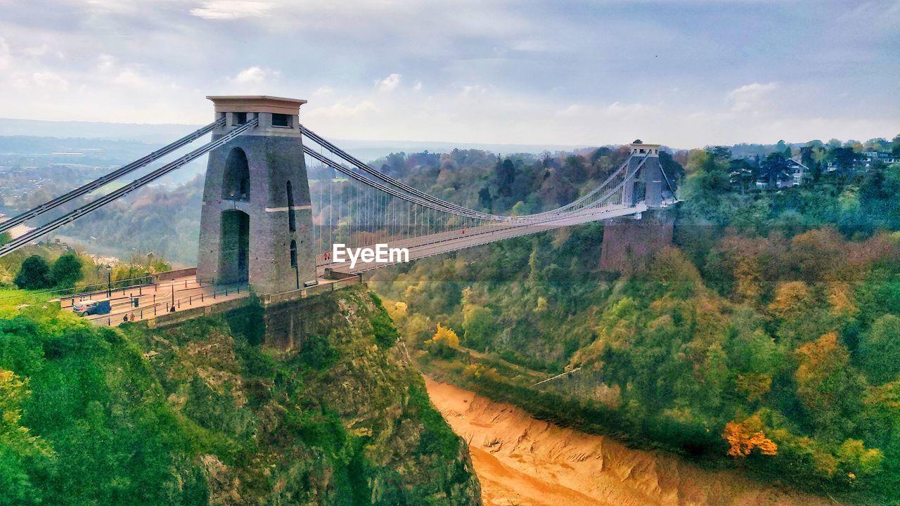 Bridge Over Mountain Against Cloudy Sky