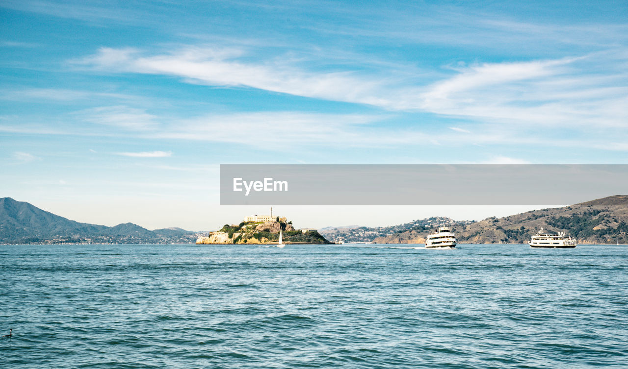 water, sky, sea, scenics - nature, beauty in nature, waterfront, cloud - sky, nautical vessel, transportation, mountain, tranquility, tranquil scene, nature, no people, mode of transportation, day, mountain range, non-urban scene, architecture, sailboat, view into land