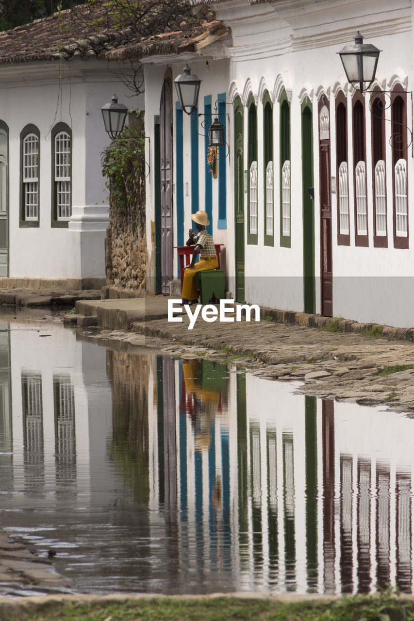 water, reflection, architecture, day, nature, built structure, building exterior, real people, one person, full length, building, waterfront, outdoors, men, adult, flood, puddle, women, rain