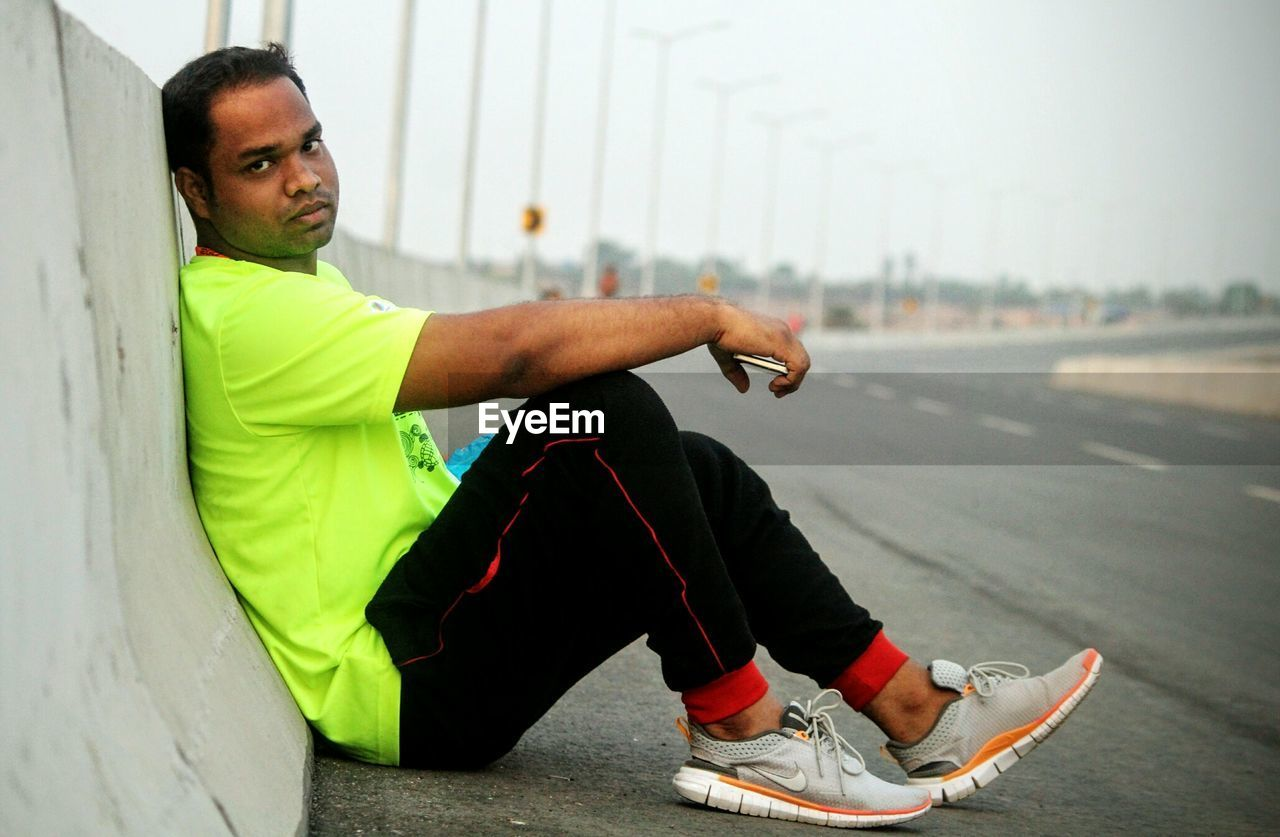 lifestyles, exercising, one person, sports clothing, real people, healthy lifestyle, sitting, young adult, men, side view, jogging, leisure activity, young men, day, full length, road, sportsman, outdoors, sport, athlete, city, one man only, close-up, adult, adults only, people