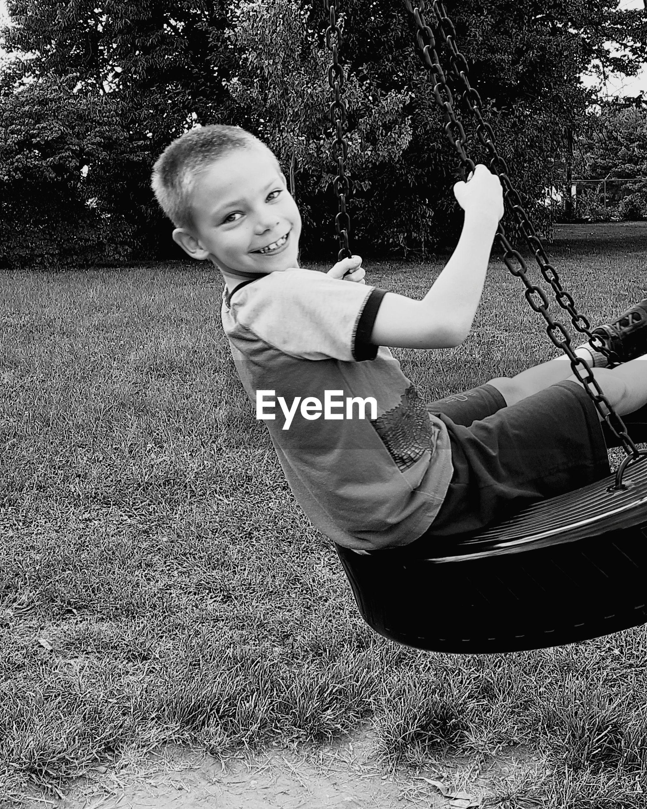 Portrait of boy on tire swing