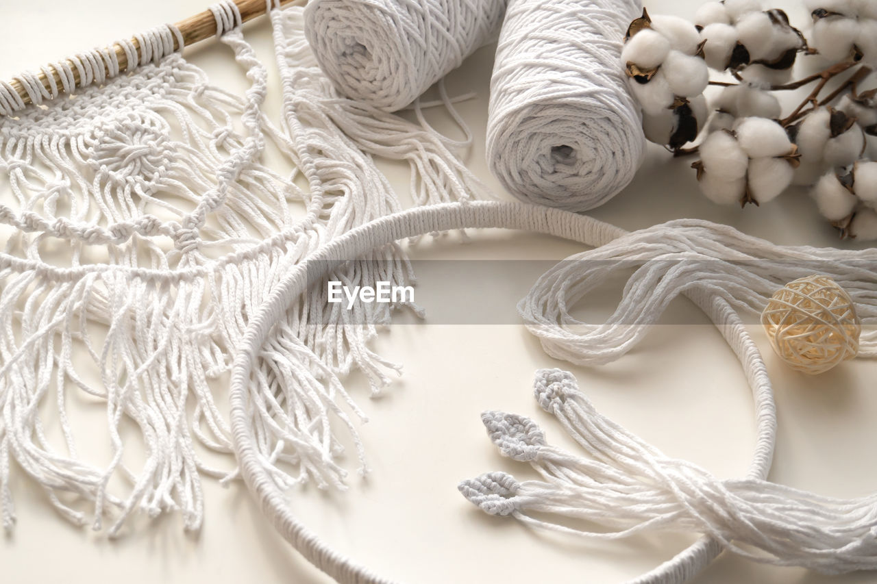 HIGH ANGLE VIEW OF ROPE TIED ON WHITE TABLE