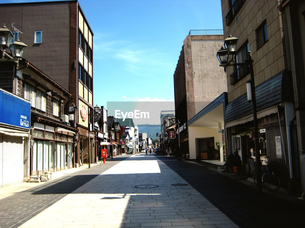 building exterior, architecture, city, built structure, street, sky, the way forward, day, direction, incidental people, nature, sunlight, building, residential district, road, footpath, outdoors, diminishing perspective, cloud - sky, shadow