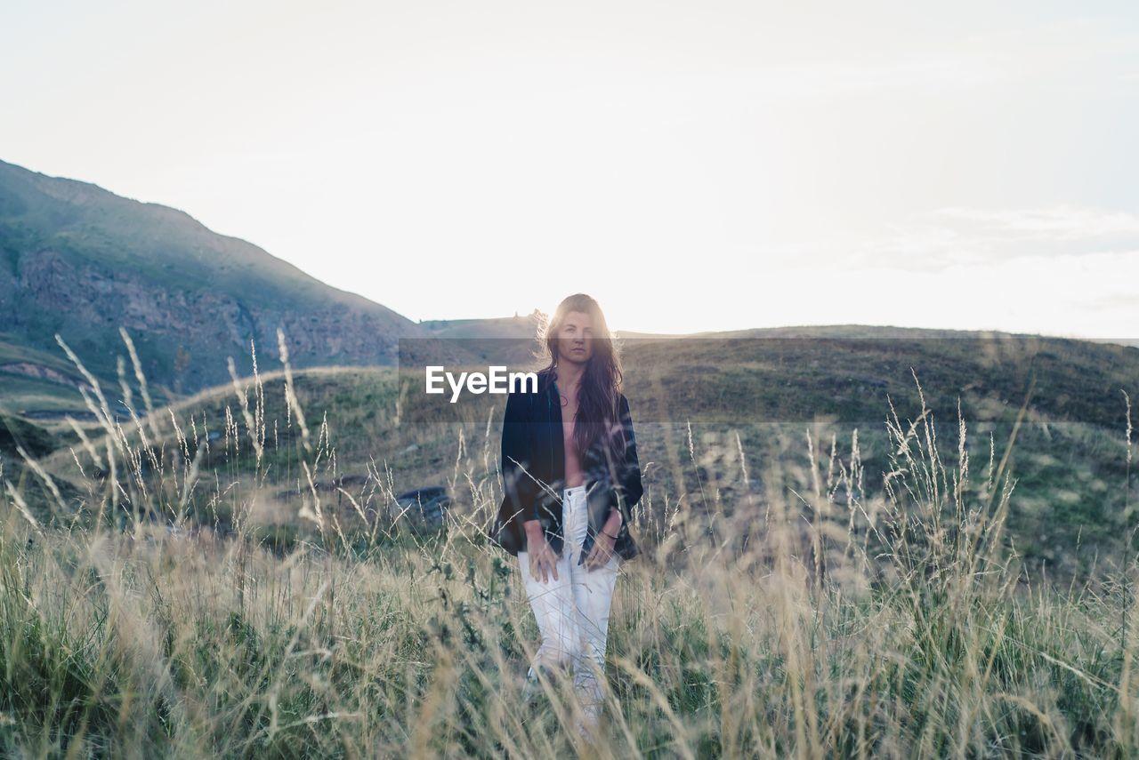 Portrait of woman standing on grassy landscape against sky