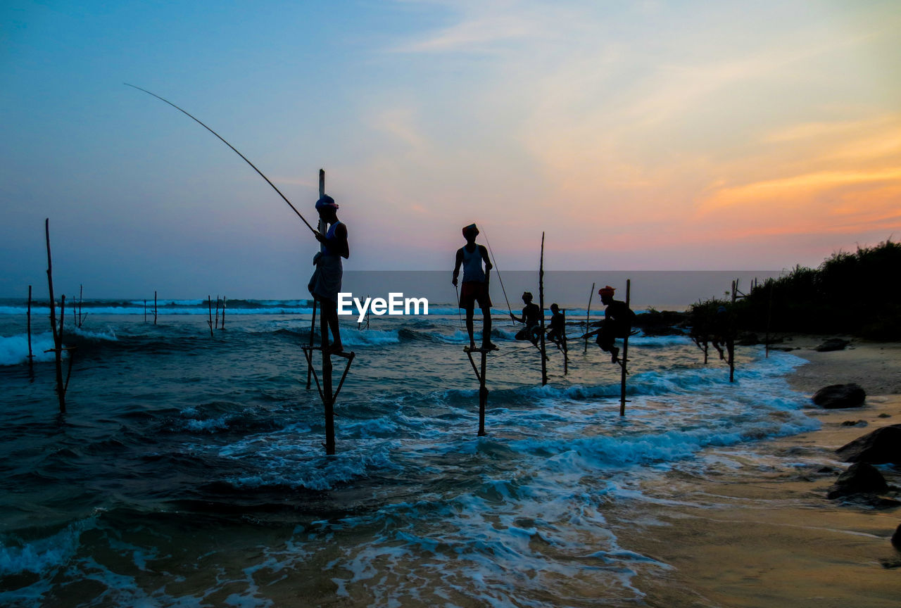 sky, water, sea, sunset, real people, fishing, men, silhouette, leisure activity, group of people, lifestyles, rod, beauty in nature, fishing rod, people, scenics - nature, activity, sport, standing, fisherman, horizon over water, outdoors, fishing industry