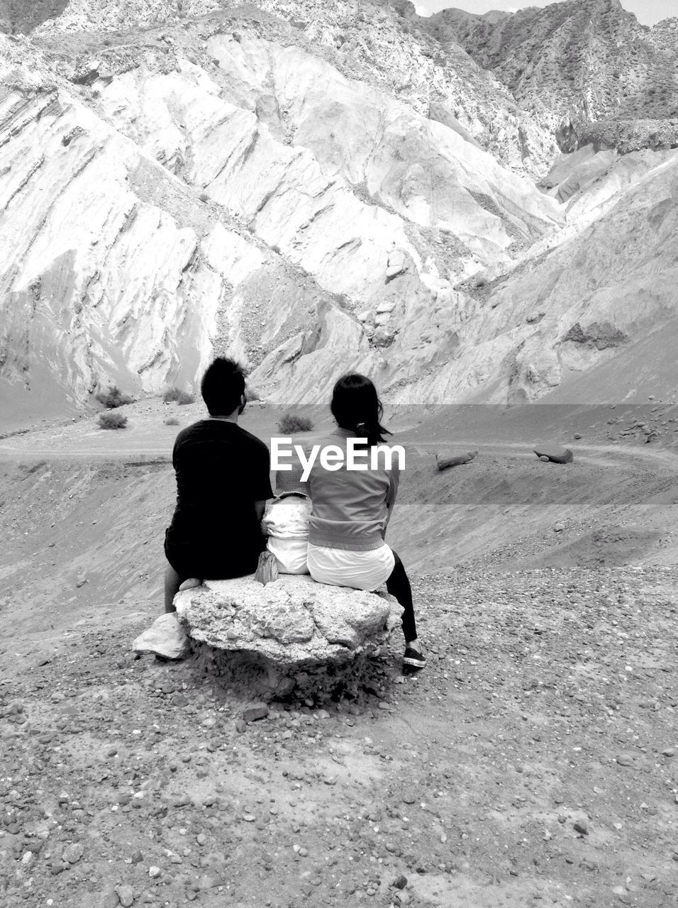 rear view, togetherness, mountain, two people, leisure activity, lifestyles, real people, women, nature, men, people, sitting, full length, beauty in nature, adult, non-urban scene, day, scenics - nature, mountain range, vacations, couple - relationship, outdoors
