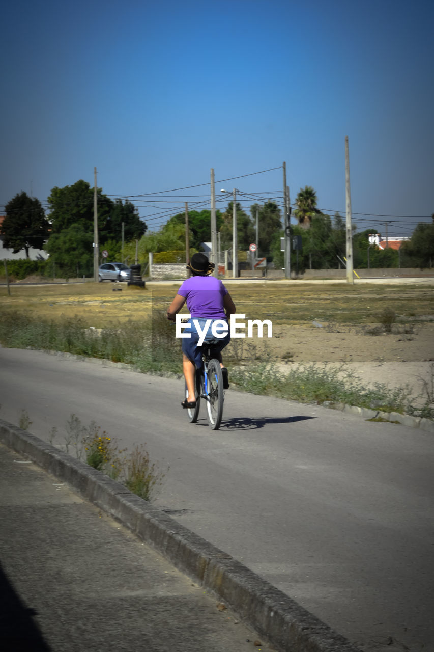 bicycle, cycling, transportation, riding, full length, road, real people, land vehicle, men, leisure activity, mode of transport, rear view, outdoors, one person, clear sky, cycling helmet, day, lifestyles, the way forward, tree, motion, bmx cycling, sky, nature, mountain bike, grass, sportsman, people
