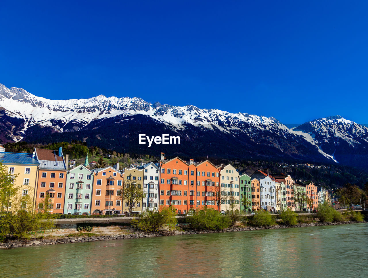 architecture, water, mountain, built structure, building exterior, building, sky, beauty in nature, waterfront, scenics - nature, nature, day, cold temperature, blue, winter, no people, snow, clear sky, mountain range, snowcapped mountain, outdoors