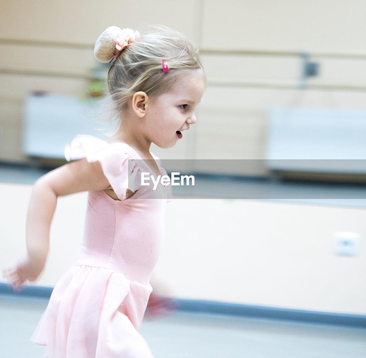 Side View Of Cute Girl Ballet Dancing In Studio