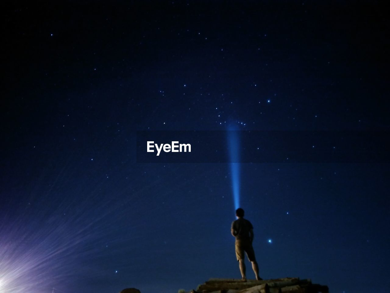Man With Flashlight Standing Against Sky At Night