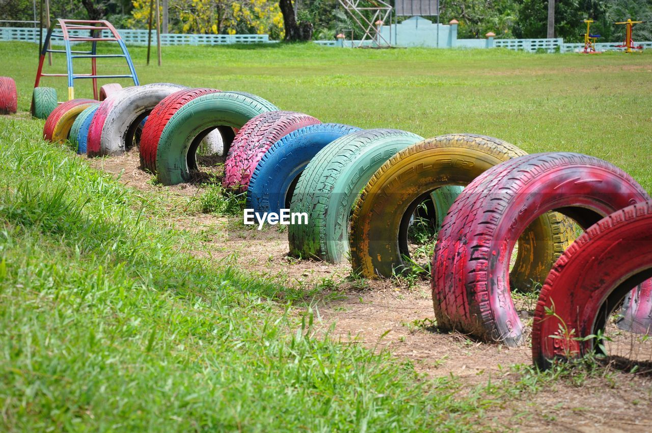 grass, plant, wheel, field, land, day, no people, tire, in a row, nature, green color, multi colored, transportation, outdoors, metal, land vehicle, growth, large group of objects, architecture, mode of transportation