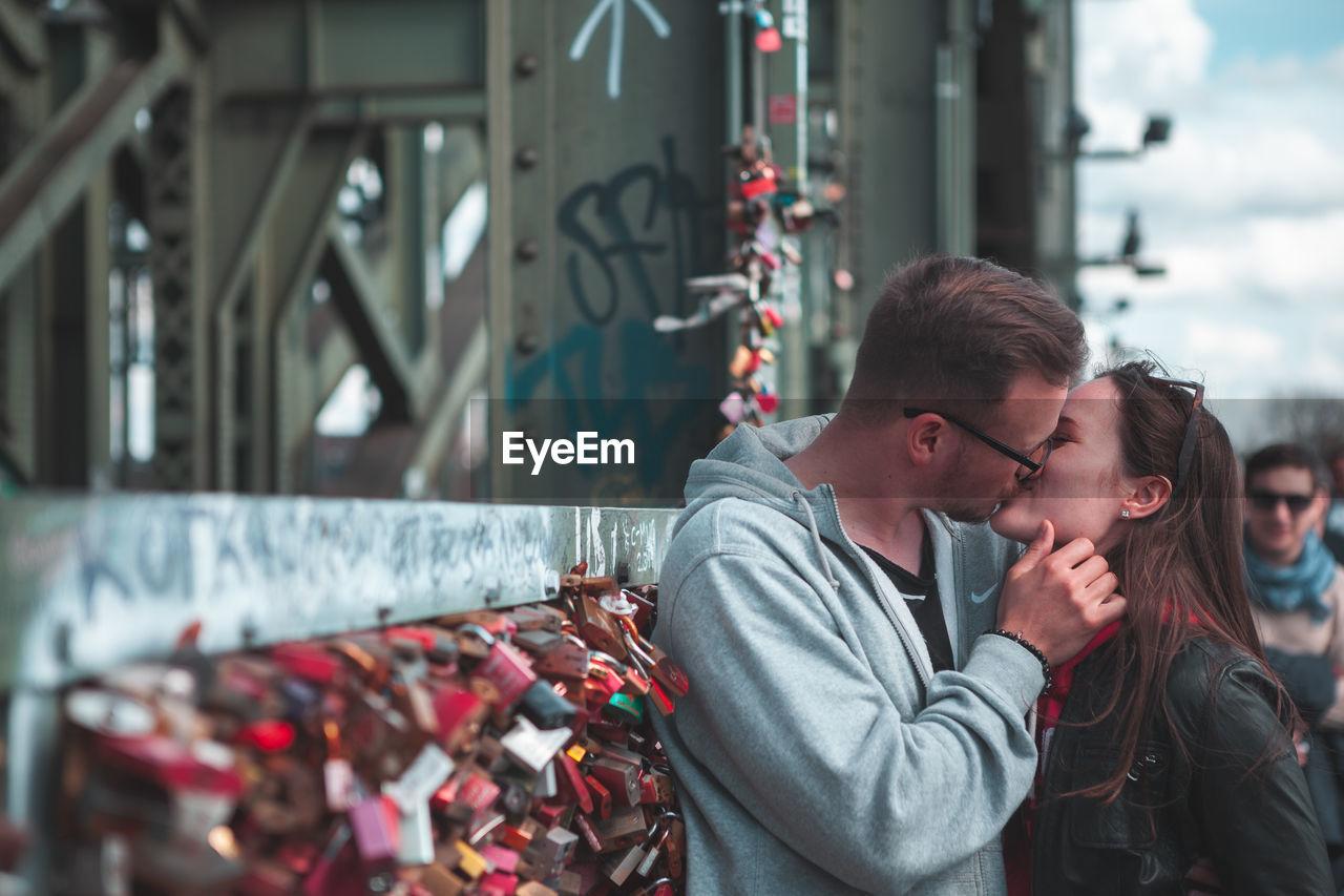 Couple kissing by love locks on bridge in city