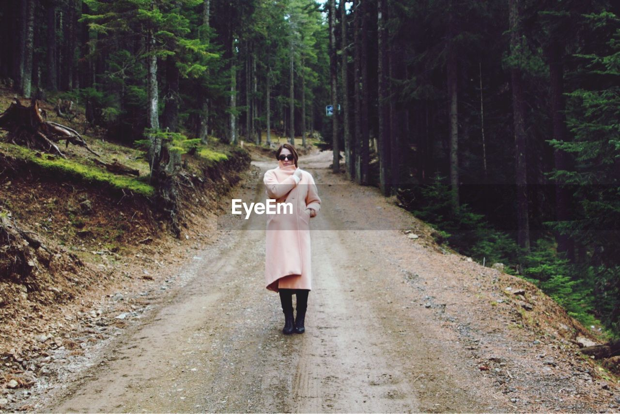 Full Length Of A Woman Standing On Road In Forest