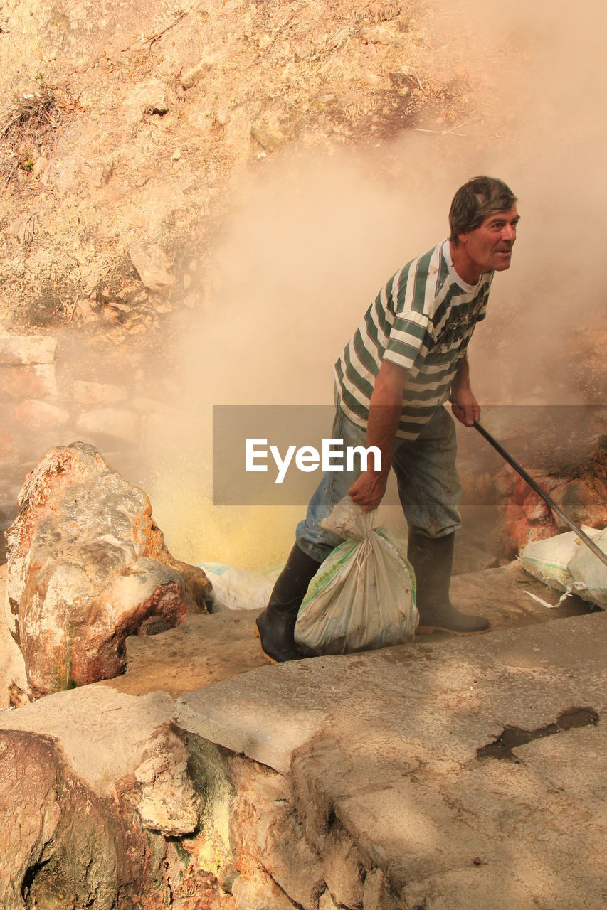 Full Length Of Worker Holding Sack At Construction Site
