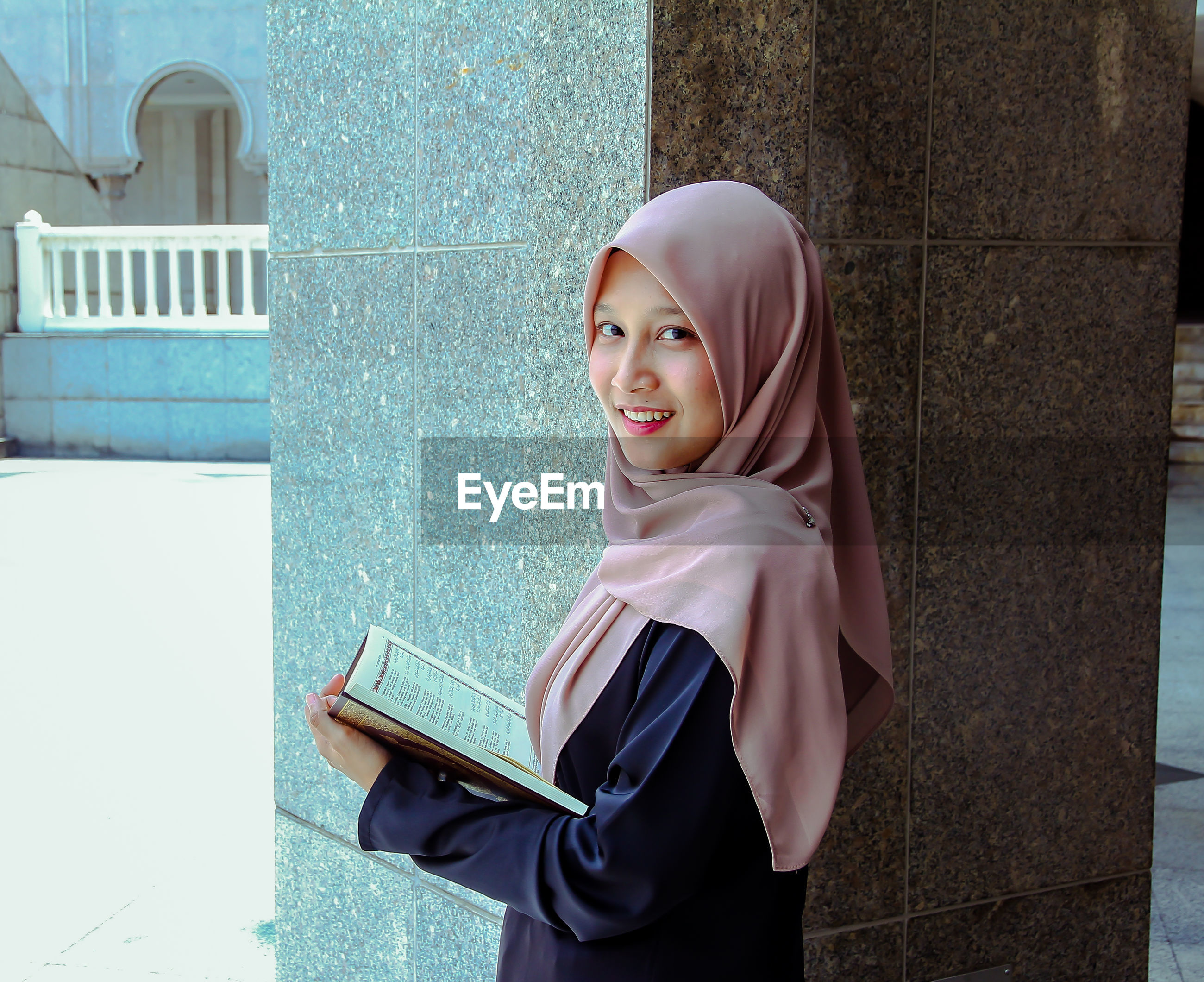 Portrait of young woman wearing hijab while reading holy book at mosque