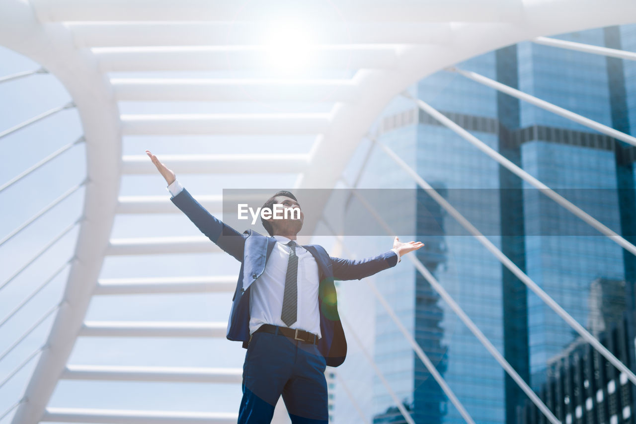 Low angle view of businessman with arms outstretched standing against buildings in city