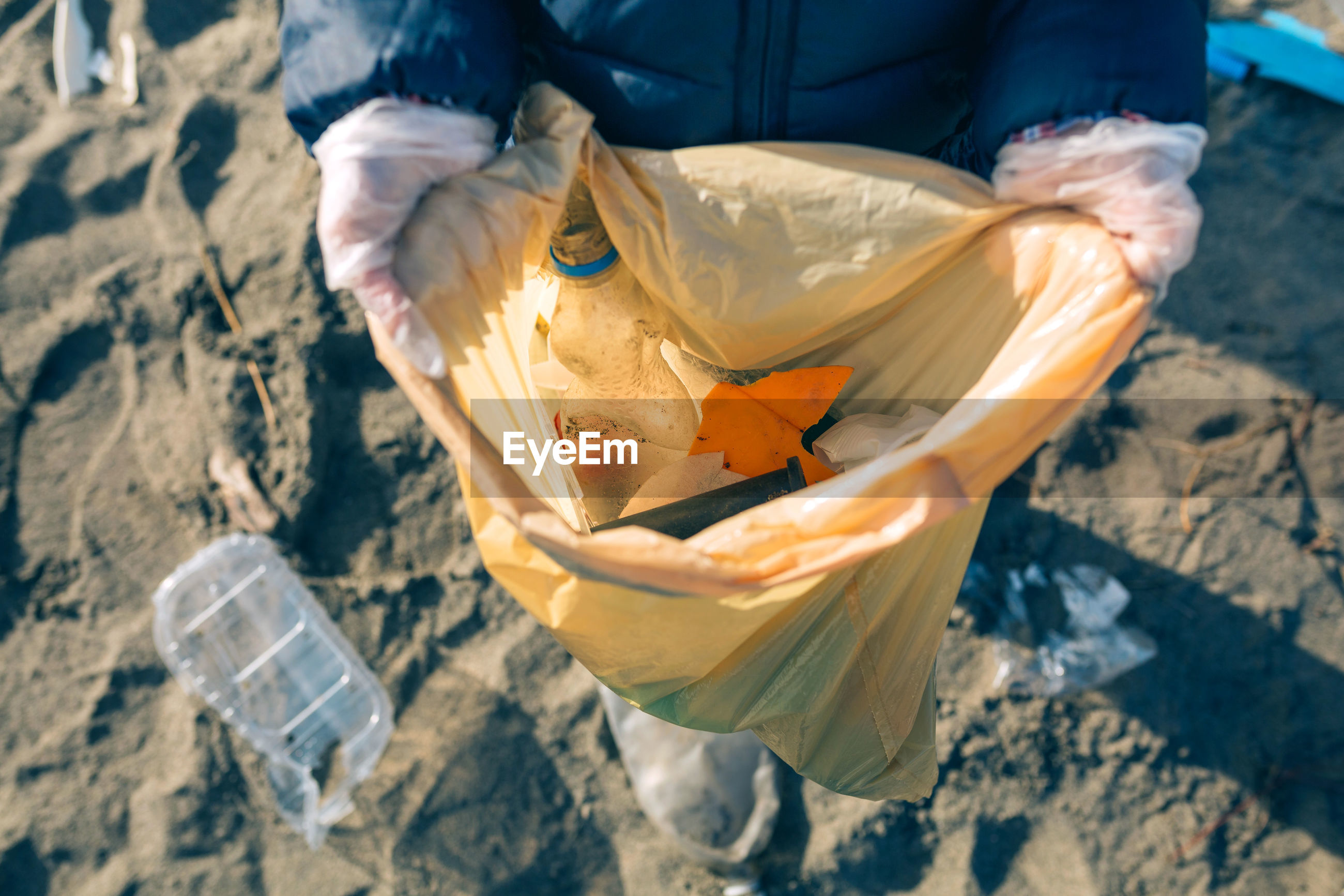 Low section of person collecting garbage