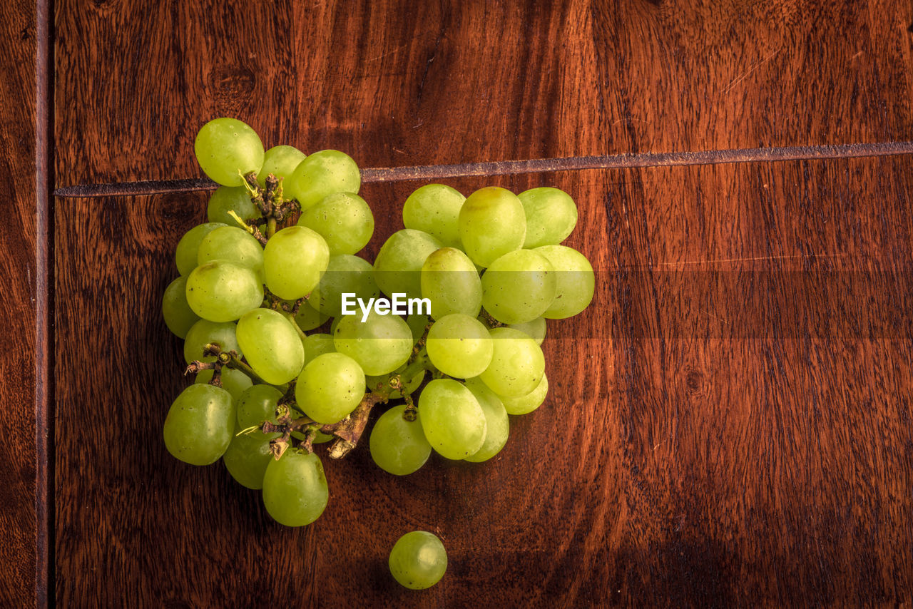 food and drink, food, healthy eating, fruit, wood - material, wellbeing, freshness, green color, no people, indoors, directly above, table, still life, high angle view, large group of objects, close-up, grape, wood, organic, citrus fruit, wood grain, sour taste