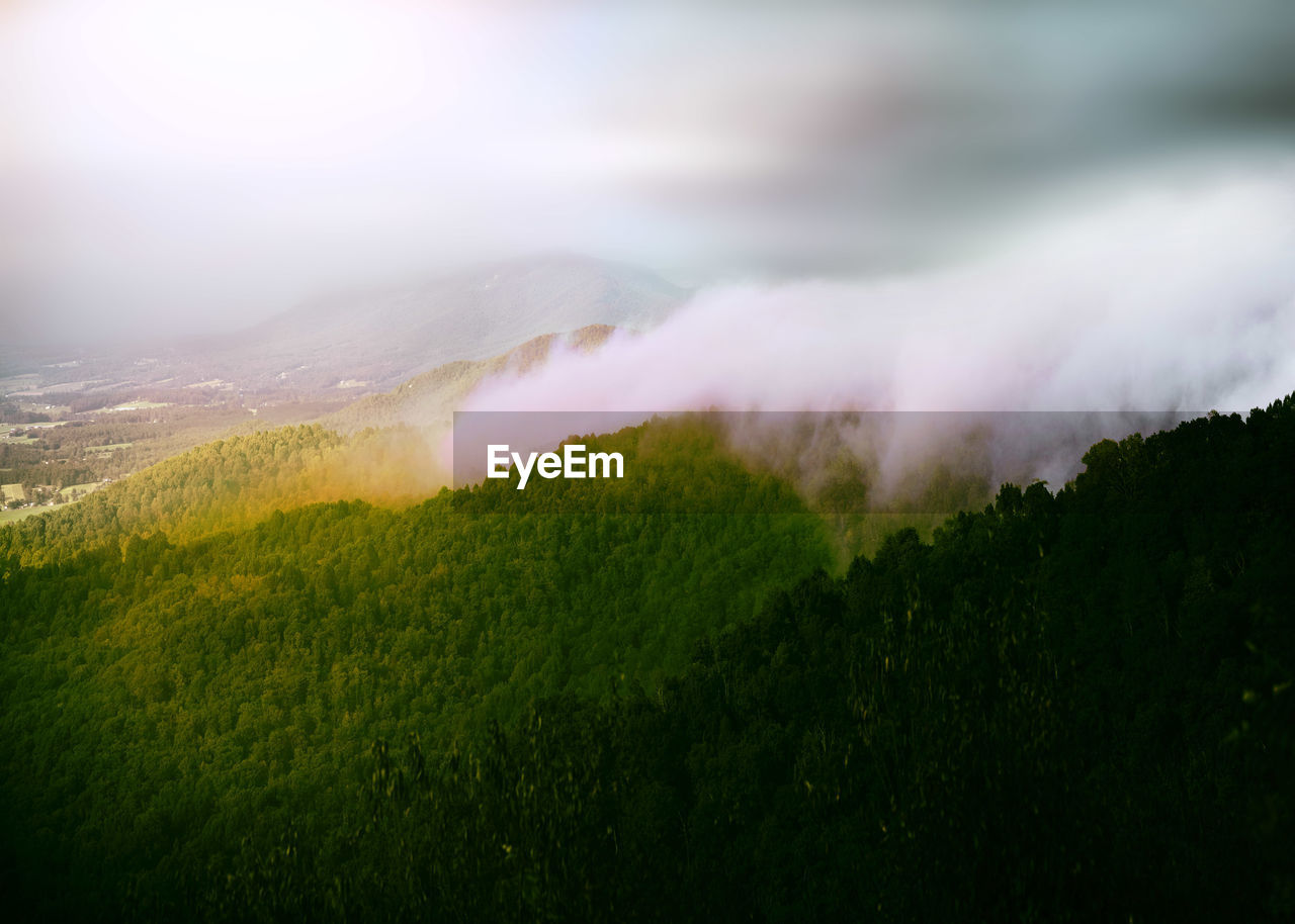 Scenic view of mountain against sky in foggy weather