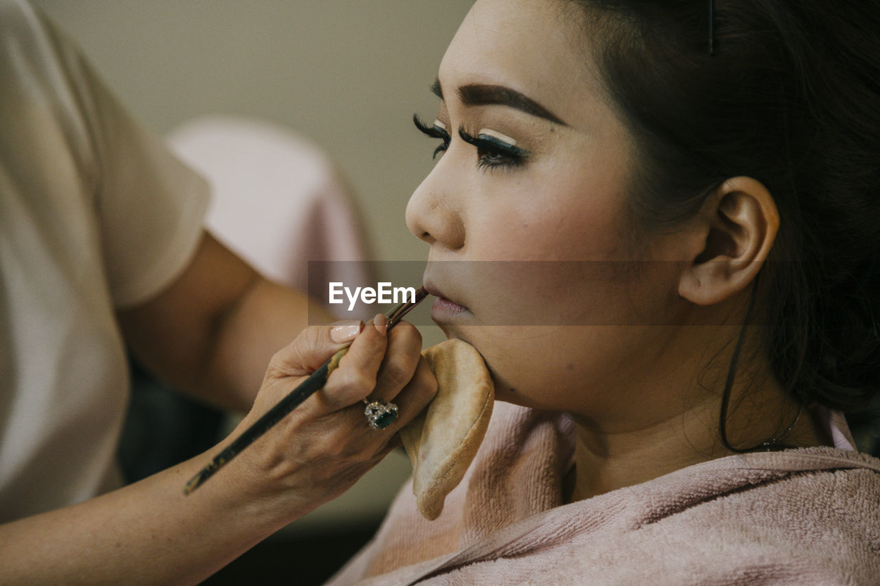 Make-up artist applying lipstick on fashion model