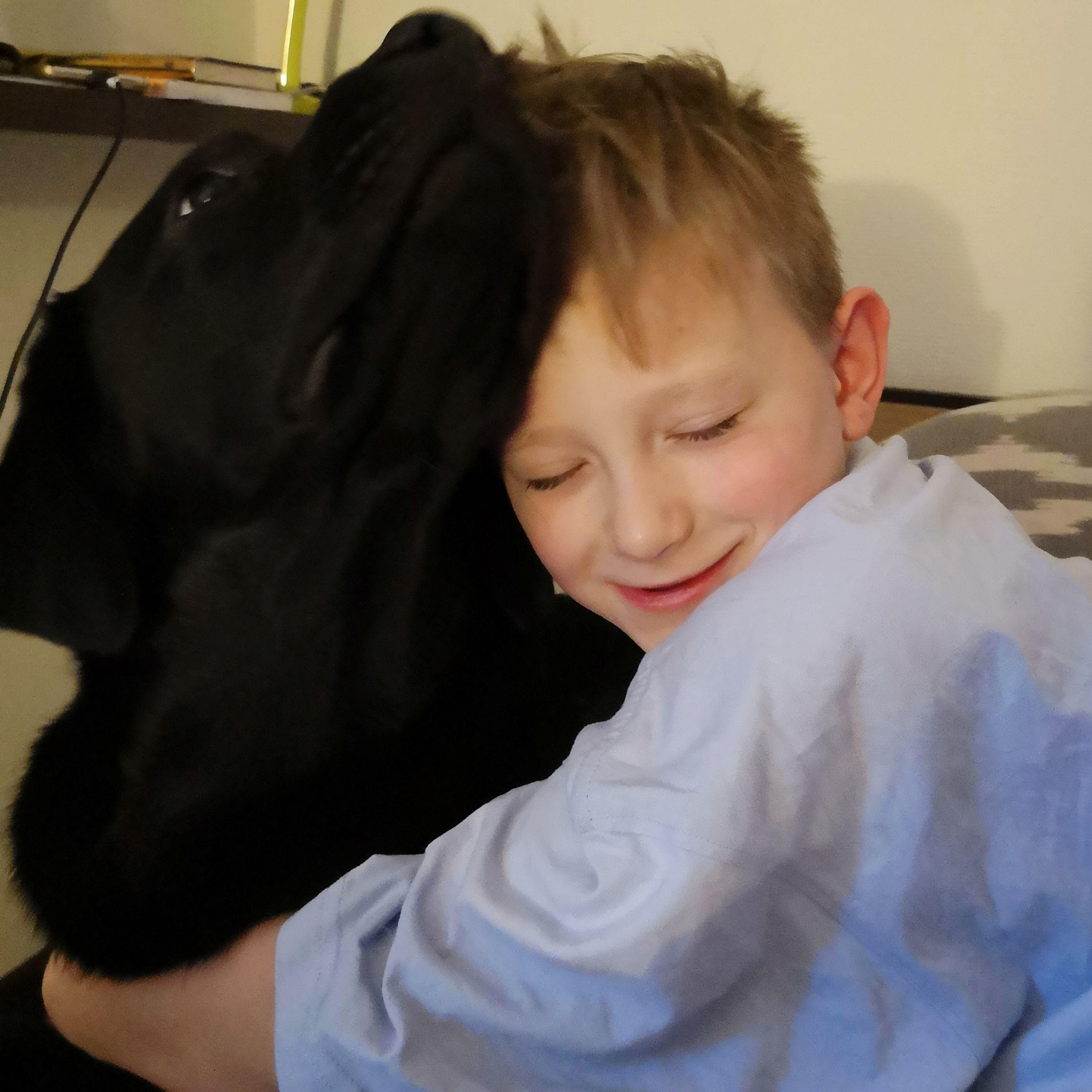Close-up of boy embracing dog at home